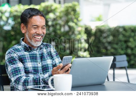 Smiling Happy Mature Man With White Stylish Short Beard Using Smartphone Gadget Serving Internet At
