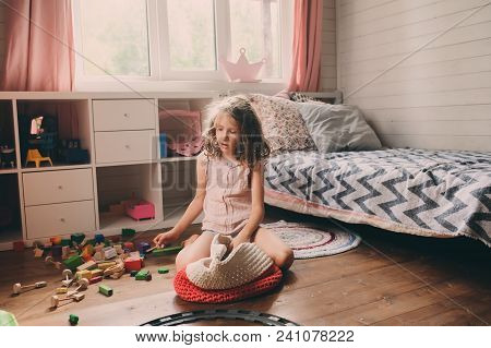 Child Girl Cleaning Her Messy Room And Put Toys In Basket