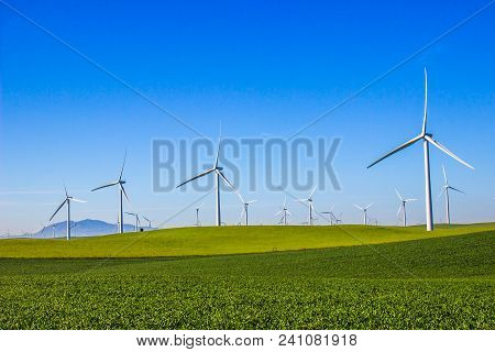 Three Bladed Energy Producing Windmills In Foothills