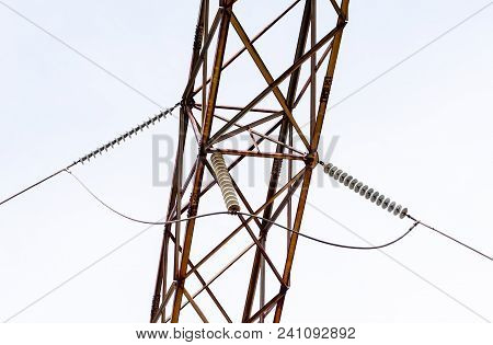 Metal Frame Girder With Insulators Holding Power Cable Passing Underneath.