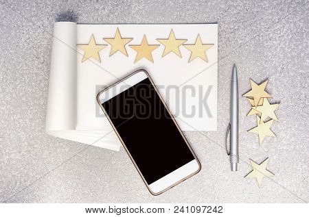 Mobile Phone, Empty Paper Notebook, Pen, Five Wooden Stars In A Row And Group Of Stars At The Side O