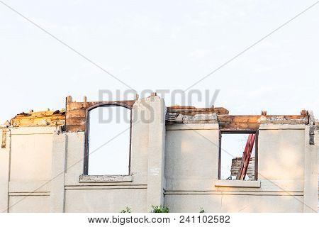 Horizontal Image Of The Upper Half Of An Old Stucco Home With Two Windows And The Roof  Been Torn Of