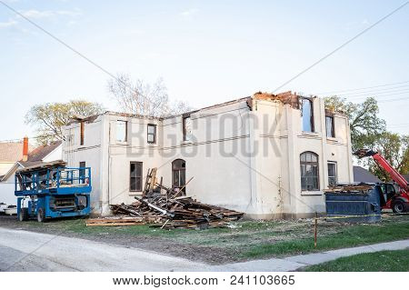 Horizontal Image Of An Old Stucco Apartment Complex Being Torn Down By Heavy Machinery.