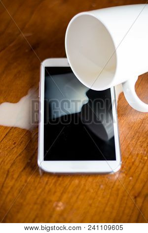 Spilled Coffee On A Phone With A Cup Nearby
