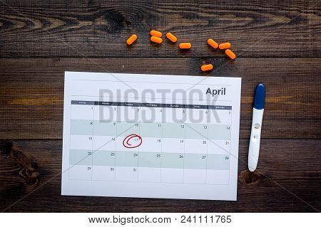 Planning Pregnancy. Positive Pregnancy Test Near Calendar Page And Pills On Dark Wooden Background T
