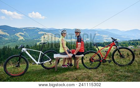 Happy Couple Sportsman Cyclists Sitting On Wooden Bench Near Bicycles, Looking To The Camera. Touris
