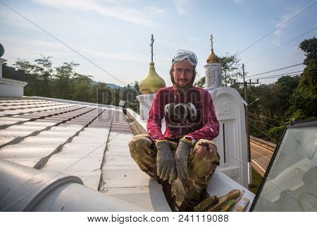 KOH CHANG, THAILAND - FEB 24, 2018: Orthodox Priest refreshes crosses on domes of the church. There are currently 10 Orthodox parishes in Thailand and Orthodoxy is practiced by 0.002% of population.