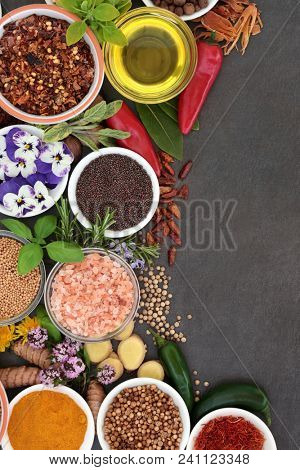 Herb and spice abstract background border with fresh and dried herbs, spices and edible flowers on slate background. Top view.