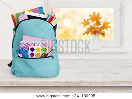 Blue School Backpack On Wooden Table Over Autumn Windowsill Background