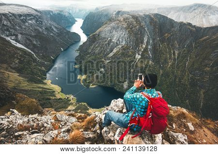 Man Backpacker Using Smartphone Relaxing On Mountain Top Traveling Alone In Norway Adventure Lifesty