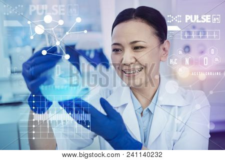 Satisfied Lab Worker. Cheerful Emotional Lab Worker Feeling Impressed And Smiling While Looking At T