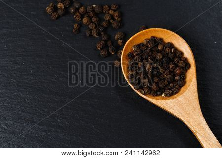 Black Pepper Spice In Wooden Spoon. Flat Lay Of Black Pepper Spice On Black Stone. Black Pepper Spic