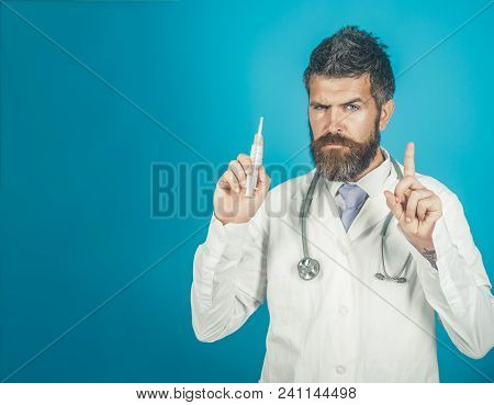 Doctor With Beard And Confident Face Expression Holds Syringe. Medicine, Healthcare, Gesture Concept