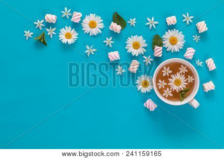 Cup Of Tea With Marshmallows And Flowers Blossom  Bouquets On Blue Surface. Flat Lay, Top View Sweet