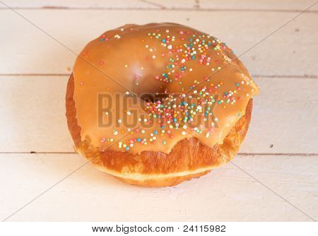 Donut Covered In Caramel Icing And Sprinkles