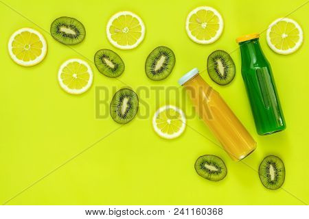 Beautiful Food Art Background. Yellow And Green Juice In Glass Bottles Sliced Lemon And Kiwi Fruit O