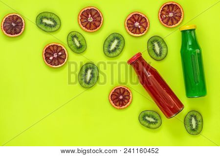 Beautiful Food Art Background. |green And Red Juice In Glass Bottles Sliced Kiwi And Blood Orange Fr