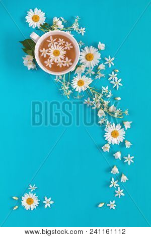 Cup Of Tea With Fresh Flowers Blossom  Bouquets On Blue Surface. Flat Lay, Top View Food Floral Back