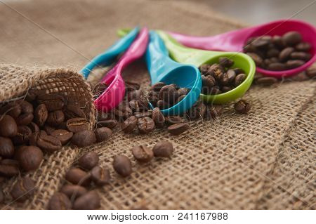Loose roasted coffee beans and color plastic dose measuring spoons on jute sack. Conceptual of recommended amount of coffee per day. Low angle selective focus and copy space poster