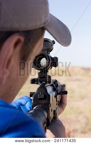 Man Aiming Through Scope At Desert Area