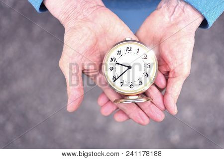 Elderly Woman Holds An Alarm Clock In Wrinkled Hands. Hands Of Elderly Grandmother. Concept Of Time