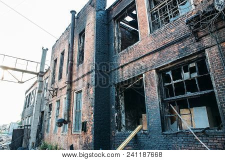 Ruins Of Burned Brick House After Fire Disaster Accident. Broken Windows With Ash And Arson