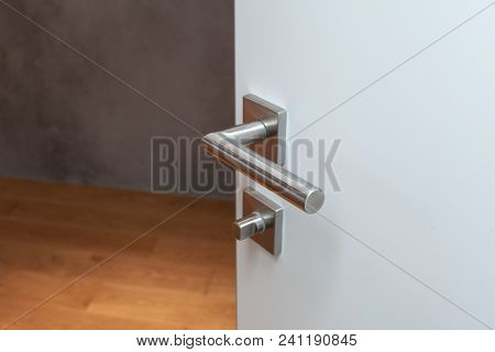 Glass Door With Metallic Handle Open In To The Empty Room With Black Wall And Wooden Floor