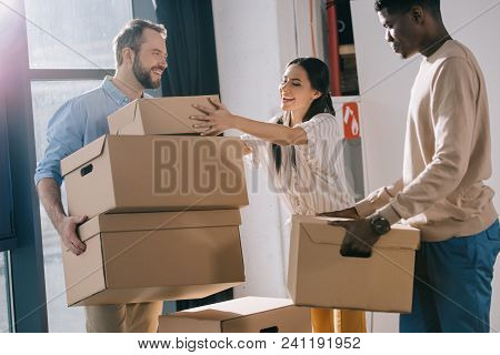 smiling multiethnic coworkers carrying cardboard boxes during relocation in new office poster