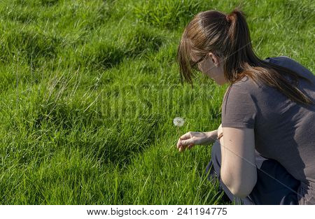 A White Caucasian Female Holding A Dandelion At The Stem Of The Flower Plant In A Field Of Green Gra