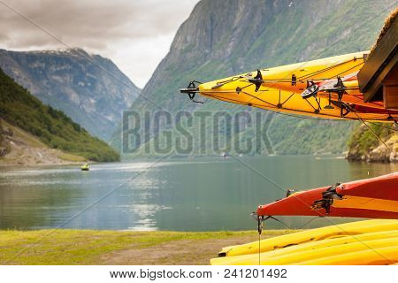 Active Lifestyle Sport Concept. Many Canoes Outdoor In Rental Center, Norwegian Fjord Landscape In T
