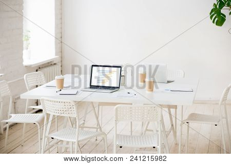 Meeting Table With Laptop And Coffee In Empty White Office Room Interior With Nobody, Shared Work De