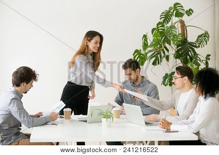 Young Woman Leader Boss Giving Team Members Documents For Review Or Consideration, Smiling Businessw