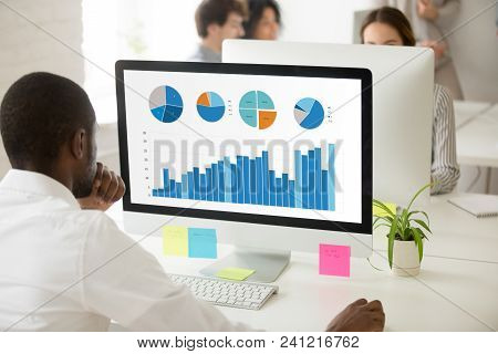 African Businessman Analyzing Graphic Data Charts Graphs Of Marketing Sales Project Performance On P