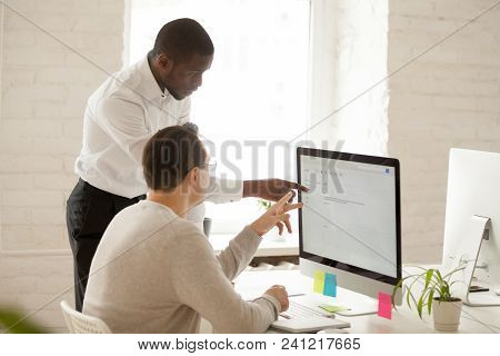 African Team Leader Helping Colleague With Computer Work Explaining Coworker New Corporate Applicati