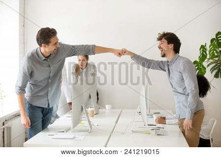 Cheerful Male Colleagues Fist Bumping Celebrating Successful Teamwork In Office, Friendly Happy Moti