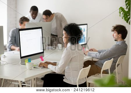 African American Woman Manager Focused On Computer Work In Multi-ethnic Corporate Office, Serious Bl