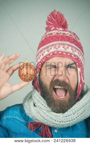 Funny Bearded Guy In Winter Hat And White Scarf Holds New Year's Toy. Hipster With Long Beard, Happy