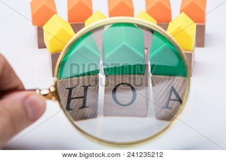Green House Model Over Homeowner Association Wooden Blocks Seen Through A Person Holding Magnifying