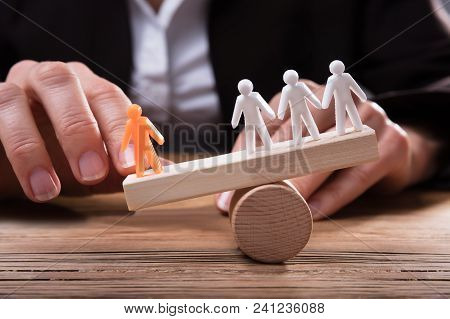 Close-up Of Businessperson Showing Orange Figure Against White Human Figures On Seesaw Over Wooden D