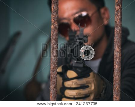 Man Aiming The Gun To An Invisible Target, With Selective Focus To Gun
