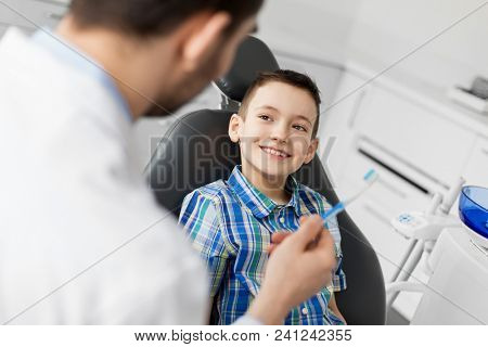 medicine, dentistry and healthcare concept - male dentist giving toothbrush to kid patient at dental clinic