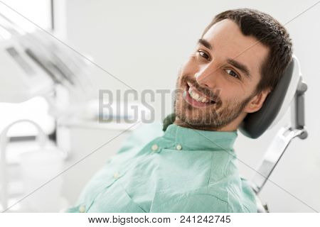 medicine, dentistry and healthcare concept - happy smiling male patient on chair at dental clinic