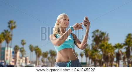 sport, technology and healthy lifestyle concept - smiling young woman with smartphone, earphones and fitness tracker listening to music and exercising over venice beach background in california poster