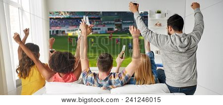 leisure, sport and people concept - happy friends with bottles of non-alcoholic beer watching soccer or football on projector screen at home