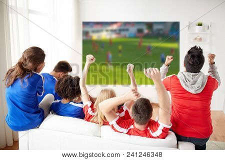 sport, leisure and entertainment concept - friends or football fans watching soccer on projector screen at home, one team wins another loses