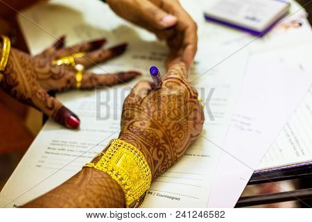 A Newly Married Indian Bengali Wife With Golden Ornament And Blacelet Signing Marriage Registration