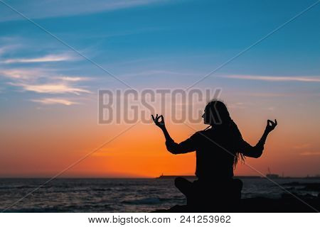 Silhouette of yoga meditation woman on the ocean during sunset.