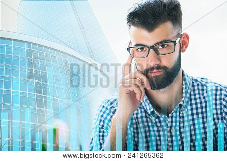 Handsome Young Businessman On Abstract City Office Background With Forex Chart. Trade, Investment An