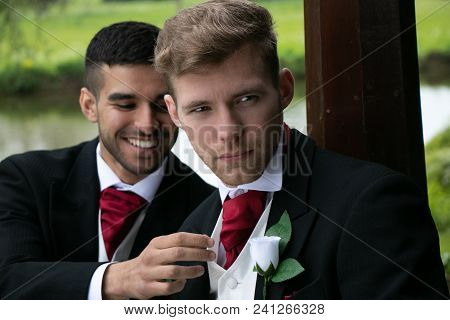 Two Gay Men Or Grooms Wearing Morning Suits Pose For Photographs By A Lake After Their Wedding Cerem