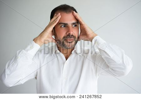Portrait Of Frightened Businessman Holding Head In Hands. Stressed Mid Adult Man Wearing White Shirt